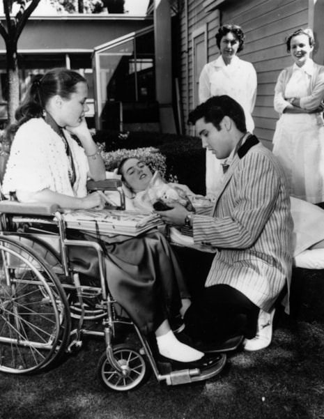 Rock 'n' roll singer Elvis Presley (1935 - 1977) chatting to two convalescent teenagers, during a visit to a hospital.  (Photo by Keystone/Getty Images)