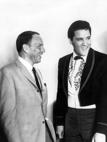 The most popular male voices in the USA, singers Frank Sinatra (1915 - 1998), left, and Elvis Presley (1935 - 1977) share a joke together in Hollywood, unusual as both of the stars are adverse to posing for press photographers. Sinatra was on the set of the film 'Frankie And Johnny' and Presley had just donated $50, 000 to the Motion Pictures Relief Fund to aid needy actors and actresses.  (Photo by Keystone/Getty Images)